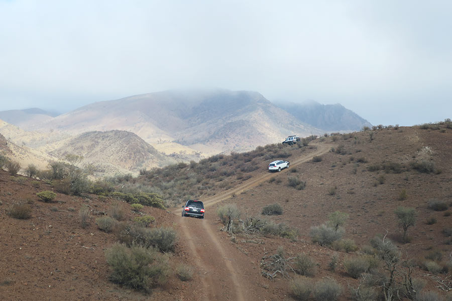 A convoy of 4WD's driving along a mountainous track with rainclouds in the distance
