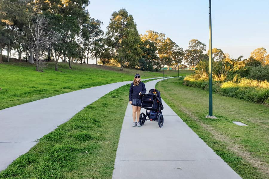 A smiling mother stands next to a stroller on a grass lined bike path
