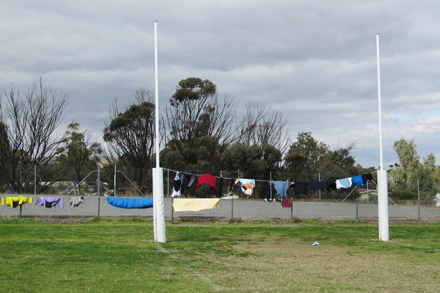 Clothes hanging on a line between two goalposts on an oval