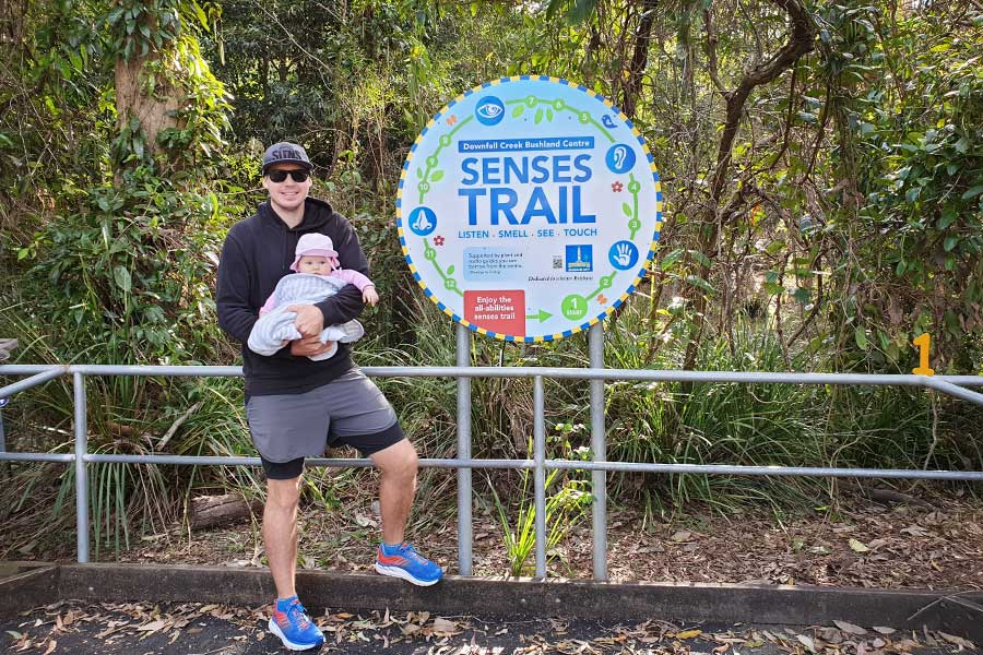 A father holding his baby in front of a sign that reads SENSES TRAIL