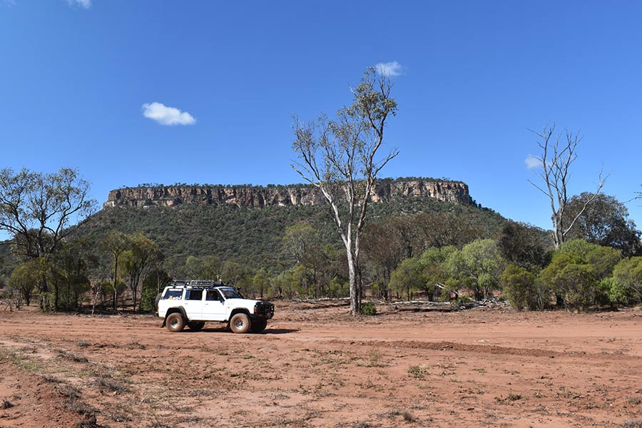 A 4WD stopped on a track in front of a sandstone formation
