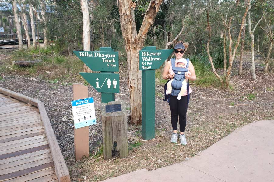 A mother wearing a baby in a carrier stands next to a Bikeway/Walkway sign