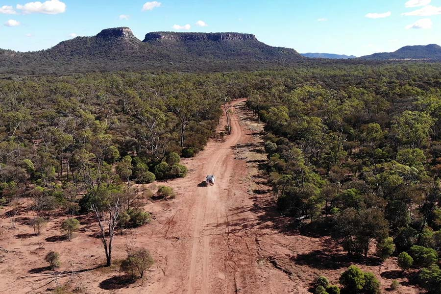 An aerial view of the remote area, with a 4WD driving along a dirt track