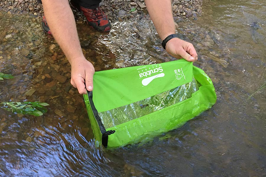 The Scrubba Washbag being filled in a river