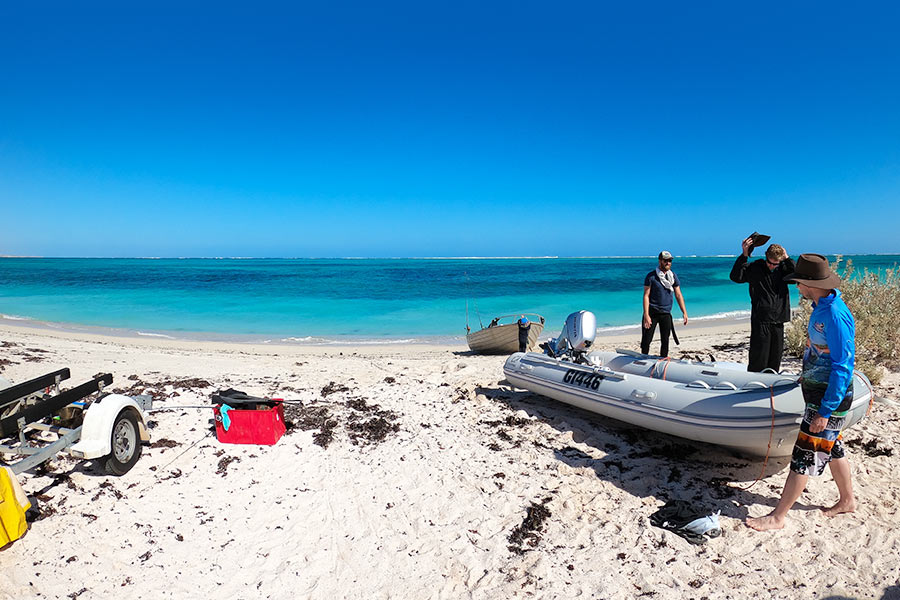 A man pulls a small boat onto the beach
