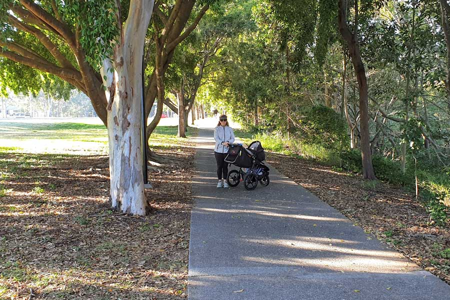 A mother stands next to a stroller on a tree lined path