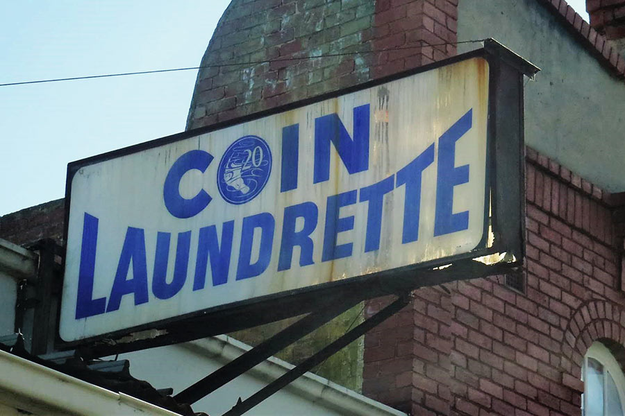 Old laundrette signage on the roof of a building