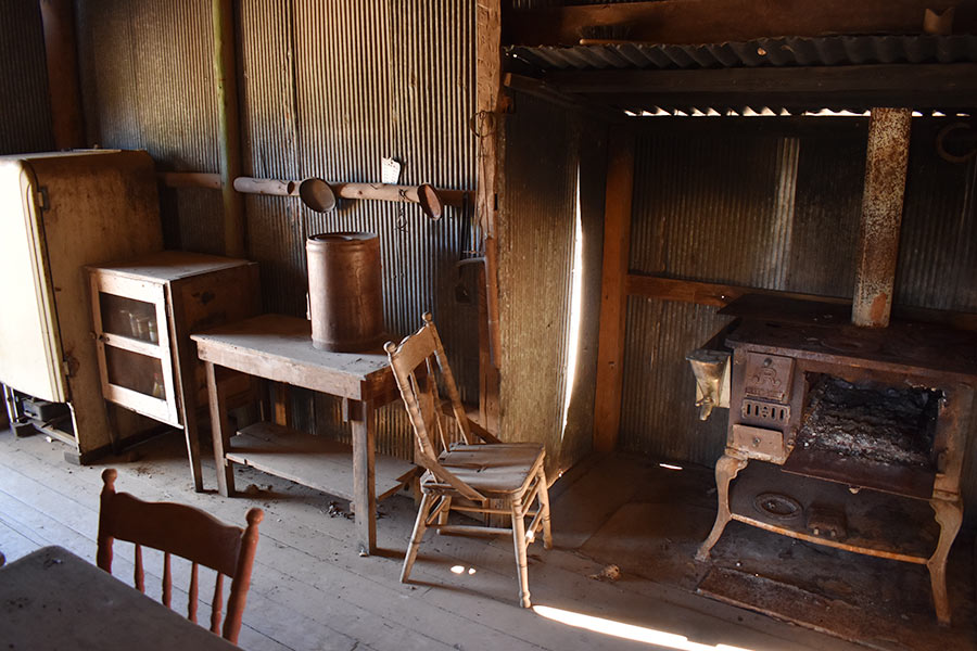 The interior of the hut containing antique furniture and a wood burning stove