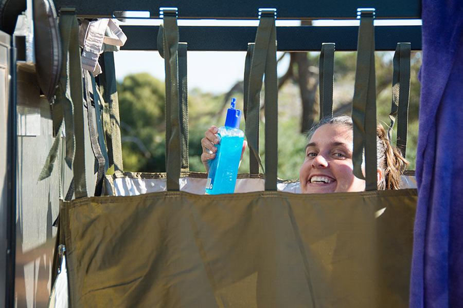 A smiling woman peers over the top of a shower screen and is holding up a bottle of body wash
