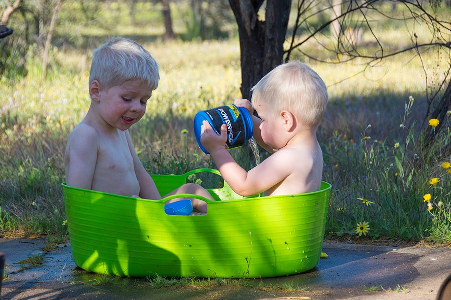 Two toddlers playing in a plastic bucket bath