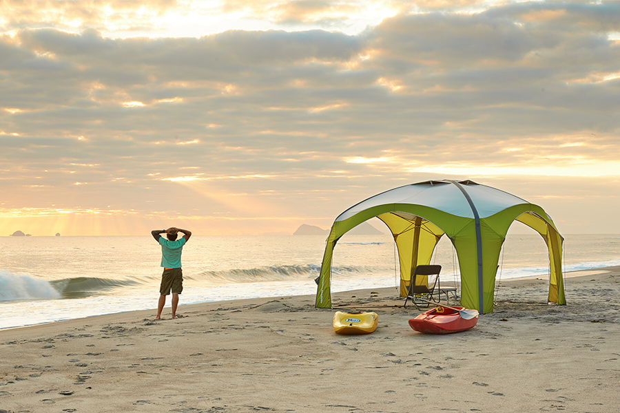 Man at the beach with a gazebo and kayaks.