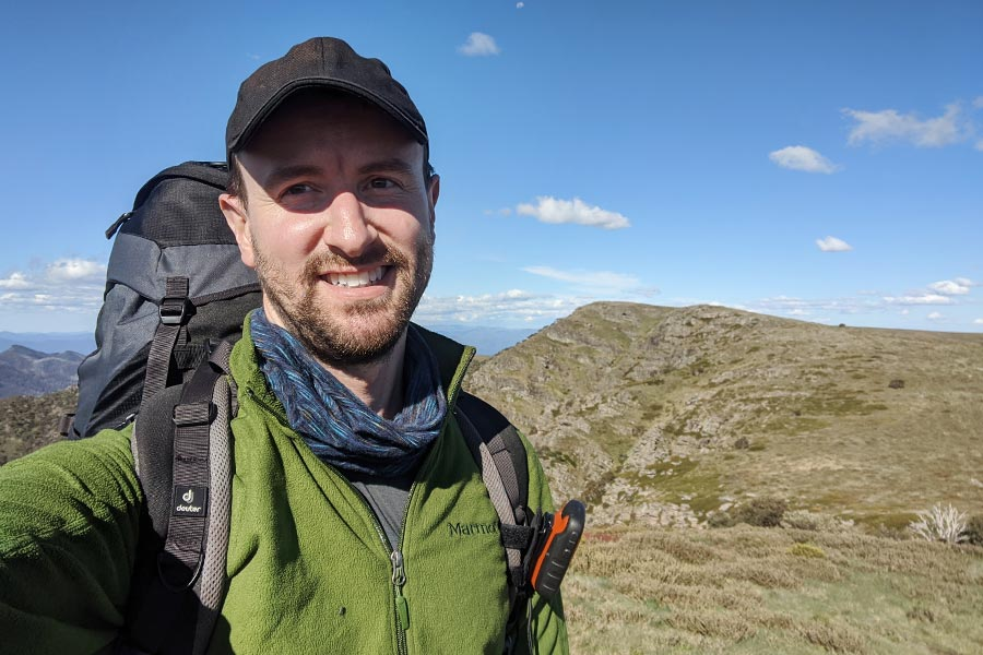 A man smiling at the camera as he takes a selfie in front of an elevated view of the mountains