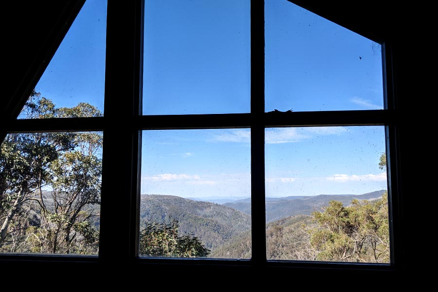Looking through a glass window at the expansive mountainous view