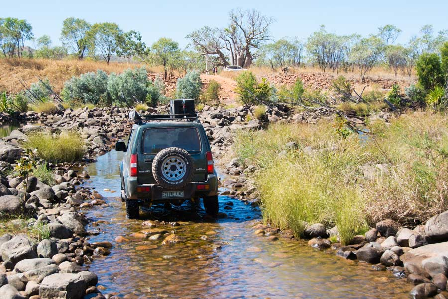 A 4WD vehicle driving along a shallow river