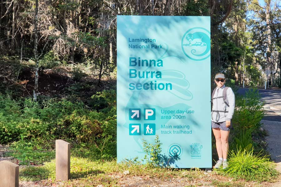 A woman stands next a large sign in a carpark, that reads Binna Burra Section.