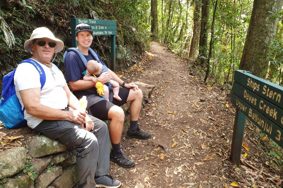 A family sit on a small rock retaining wall next to a trail in the rainforest