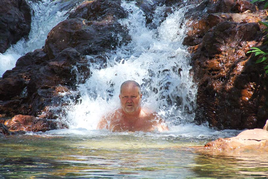 A man sits under a small waterfall in a river