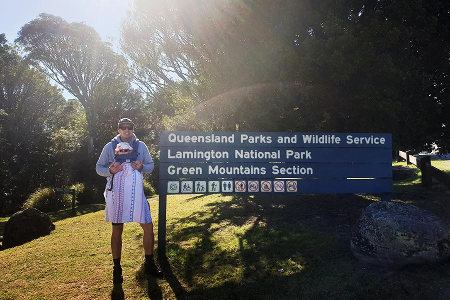 A man with a baby in a baby carrier stands next to a sign that reads Lamington National Park