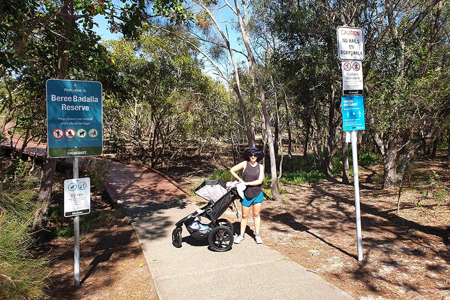 A woman stands next to a stroller on at the start of a boardwalk leading into the mangroves.