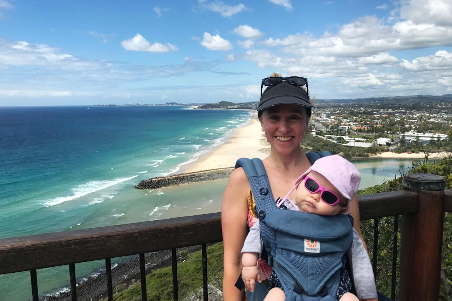 A woman wearing a sleeping baby in a carrier poses for a photo at a lookout with a beach below.