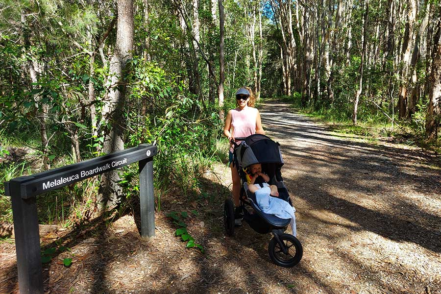 A woman stands behind a stroller with a smiling baby in it at the start of a forest trail.