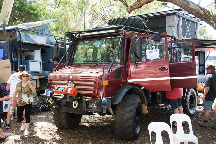 People check out a parked Unimog with it's doors open.