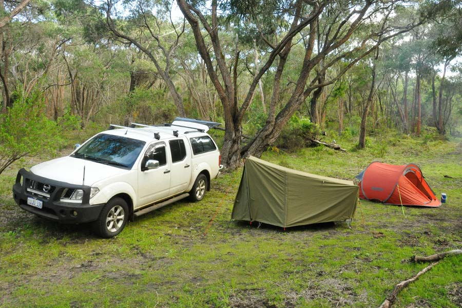 A couple of easy-to-pitch tents next to a car at a secluded campsite.