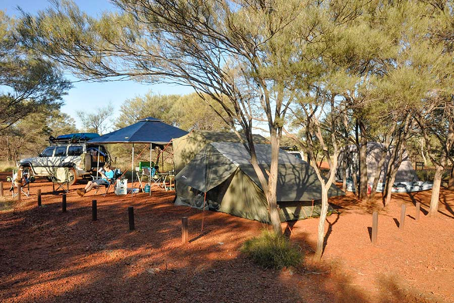 People relaxing in chairs at an outback campsite set up with tents and gazebo.
