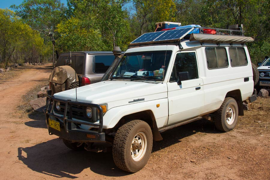 A Toyota Landcruiser parked by a dirt road, with mounted solar panels, roof racks and awning.