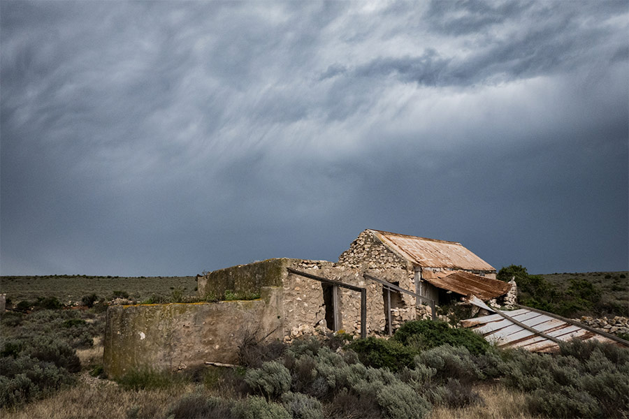 Old stone ruins on a remote island. There are dark storm clouds overhead and coastal shrubs surrounding the ruins.