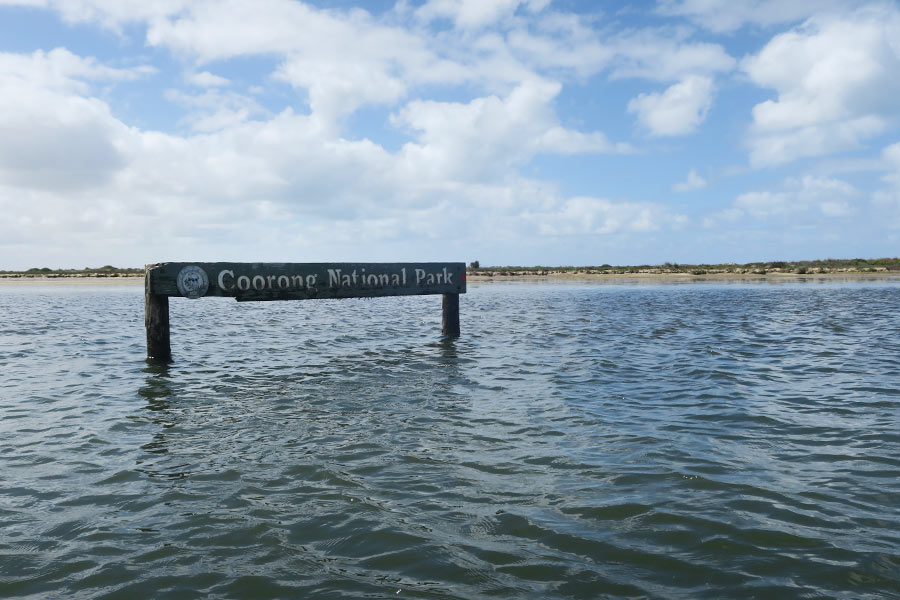 A sign, partly submerged in the water, reads Coorong National Park.