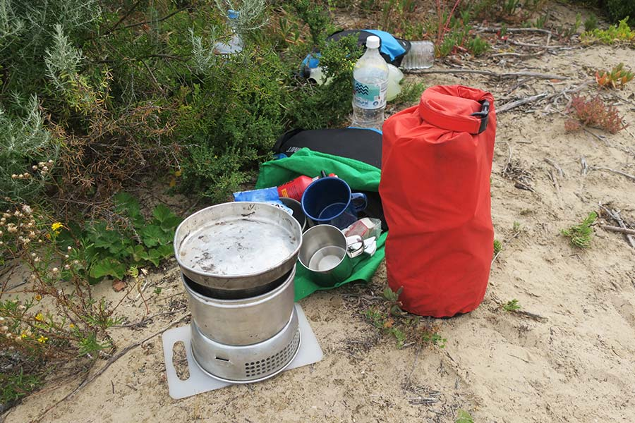 A cooking stove sits next to empty cups, water and a full dry sack.