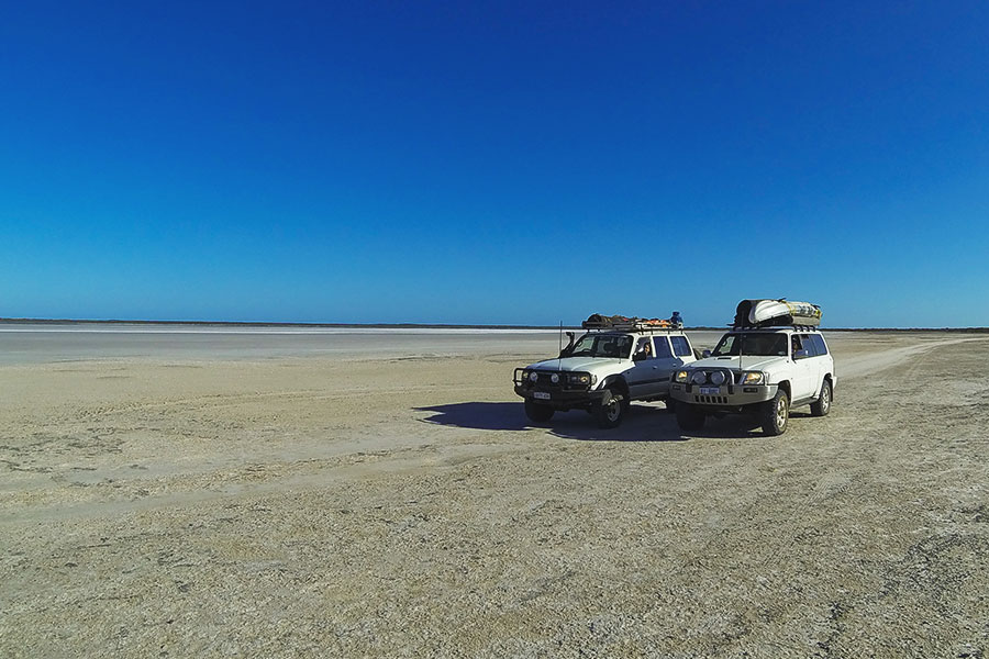 Two white 4x4 vehicles parked side by side on a salt lake with clear blue sky overhead.