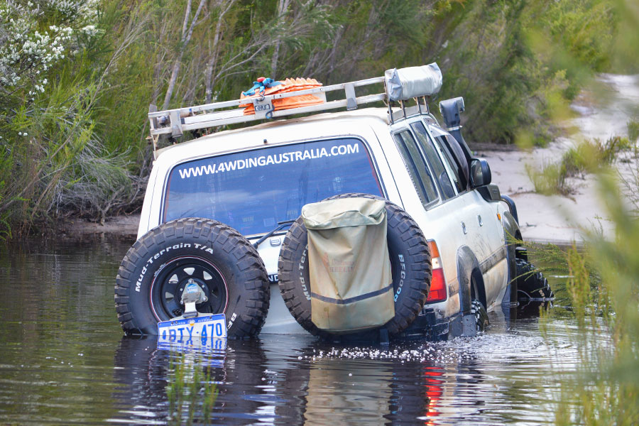 A white Land Cruiser stuck in water and leaning deeply to the left.