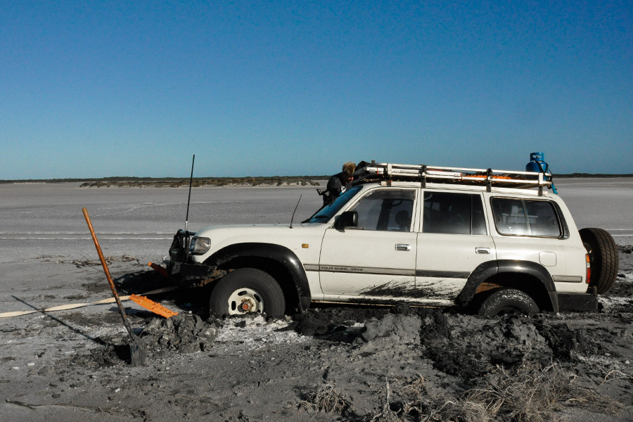 A 4WD bogged in mud with recovery gear scattered around.