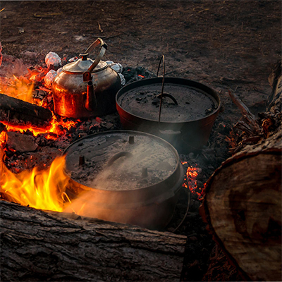 An evening scene with logs, a campfire and a couple of cast iron camp ovens plus large kettle.