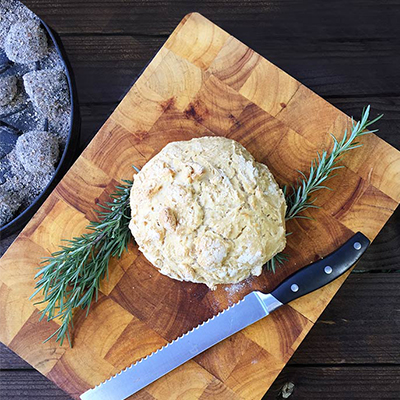 Freshly cooked damper on a chopping board next to a bread knife and springs of rosemary.