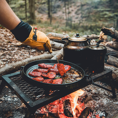 A gloved hand tends to a campfire grill that sits over flames. A blackened pot and billy sit behind and there's slices of meat being cooked.