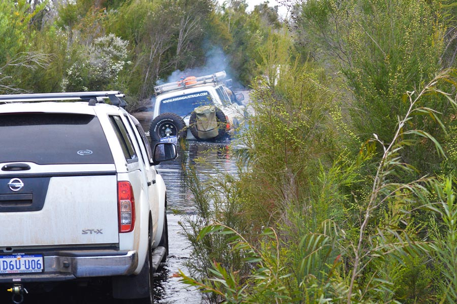Two 4x4's driving through a deep water crossing with bush foliage around.