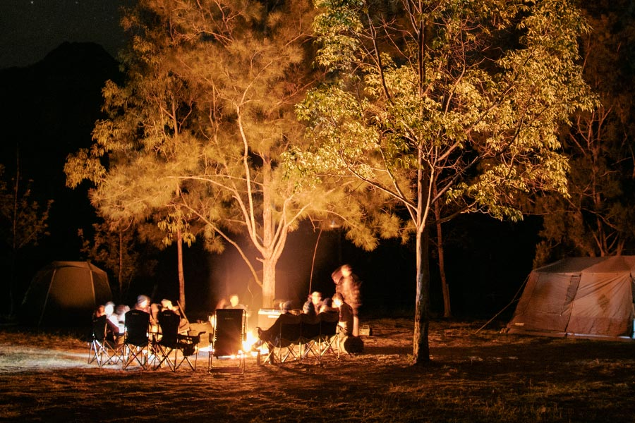 A group sitting on camp chairs around a campfire at night. The glow of the fire is illuminating the trees in the background.