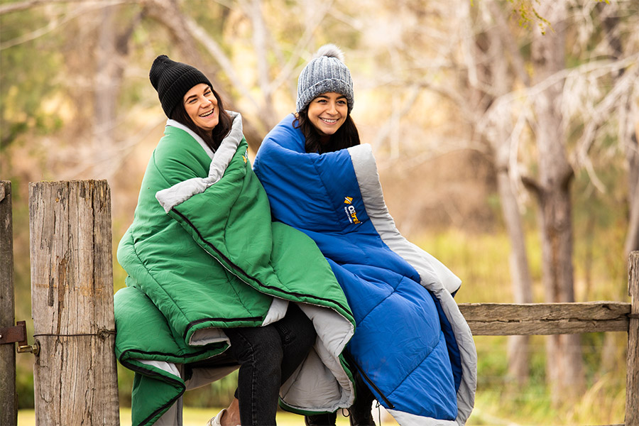 Two smiling females wearing beanies and wrapped in sleeping bags sit on a farm fence.