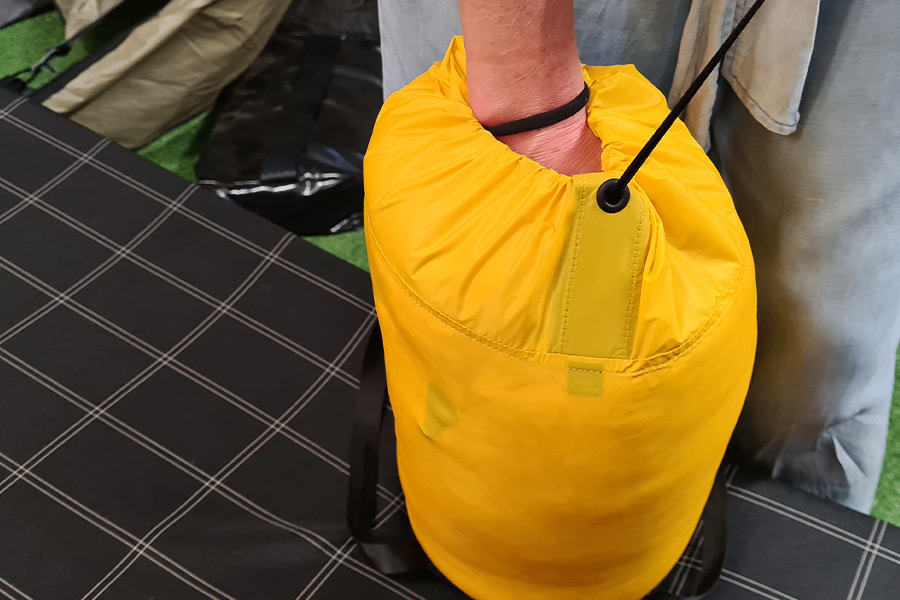 A fist is submerged inside a full sleeping bag compression sack while another hand out of shot pulls the drawstring closed.