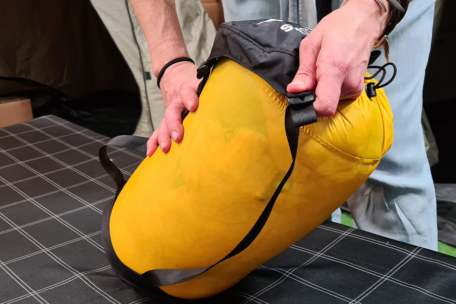 Two hands fit the black cap over the top of a yellow compression sack.