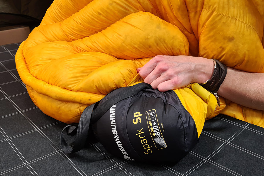 A Spark SP4 sleeping bag turned inside out and being stuffed into its compression sack.