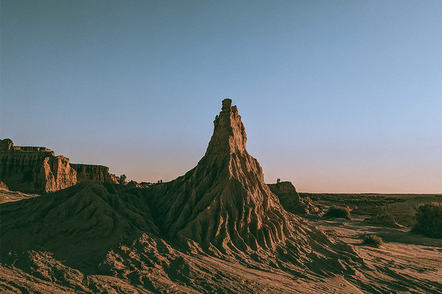 A wind-carved rock sculpture shadowed and illuminated by the setting sun at Mungo Lake.