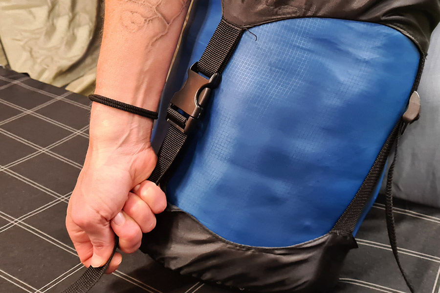 A hand pulls the black compression strap on a blue sack.