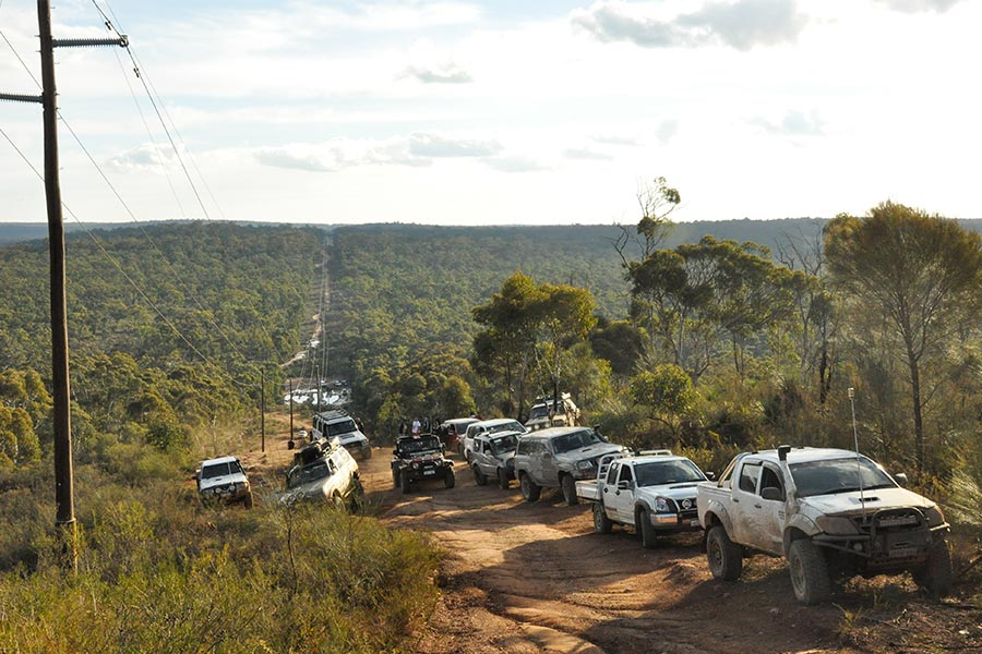 A convoy of 4WD vehicles pulled to the side of a track to allow another vehicle through.