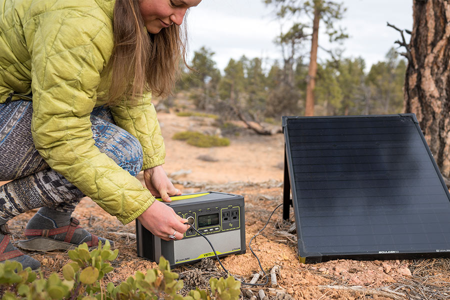 Woman plugging a goal zero solar panel into a power station outdoors.