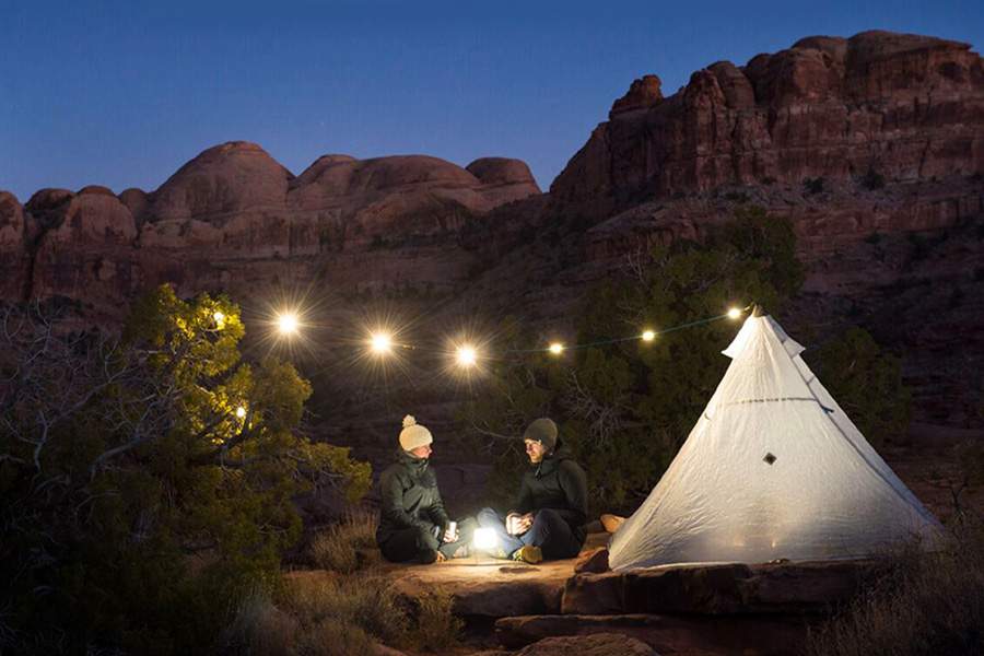 A couple sitting at dusk with their hiking tepee tent and fairy lights over camp. They're dressed for cold weather and surrounded by native trees at the base of a canyon.