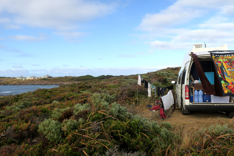 An open campervan showing washing hanging out to dry. It's parked by the ocean with coastal shrubs all around.